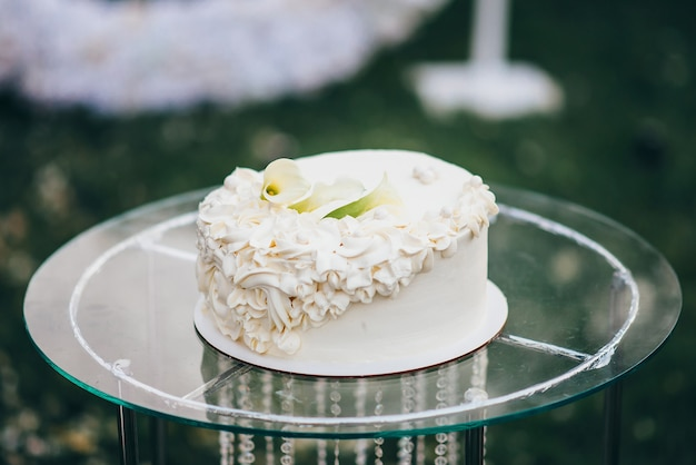 꽃의 형태로 크림으로 장식 된 단층 흰색 웨딩 케이크는 자연의 유리 테이블에 서 있습니다.