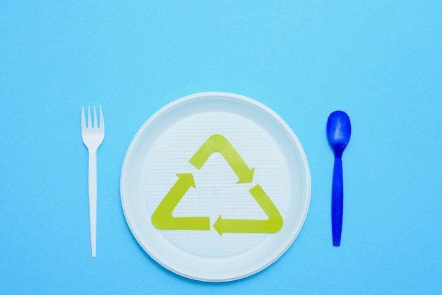 Single use, disposable tableware and recycling sign on background. spoons, forks