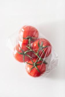 Одноразовый выпуск пластиковой упаковки. помидоры овощи в полиэтиленовом пакете