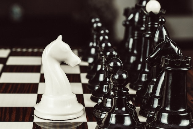 Single white chess piece against many enemies