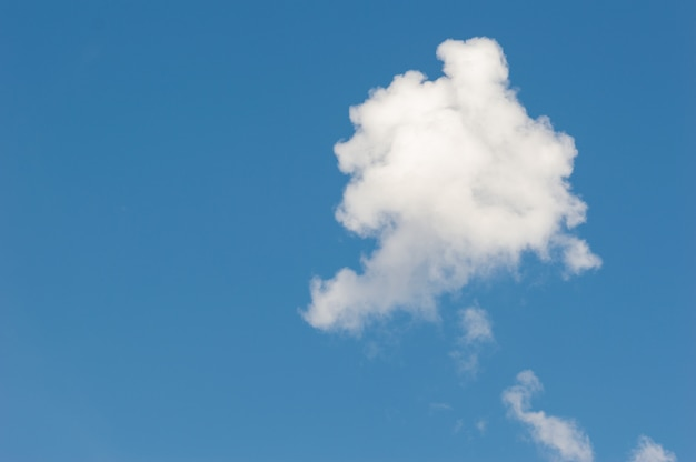 A single white cloud in the blue sky