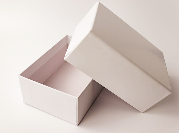 Single white color paper cardboard box on light . close up view. selective soft focus. text copy space. packing, transportation, moving, present concept