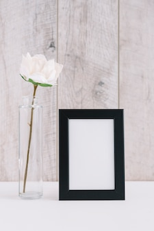 Single white flower in vase near blank picture frame