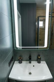 Единственная белая раковина, туалетный столик и зеркало в ванной комнате