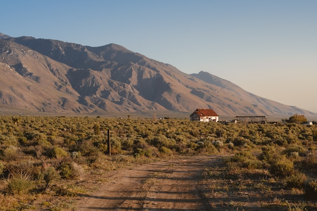 Single white house with a brown roof in california, next to the sierra nevada mountains