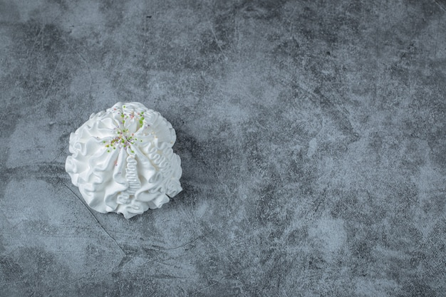 A single white isolated meringue cookie on the ground.