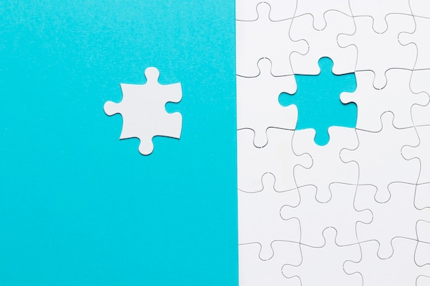 Single white jigsaw puzzle piece on blue background