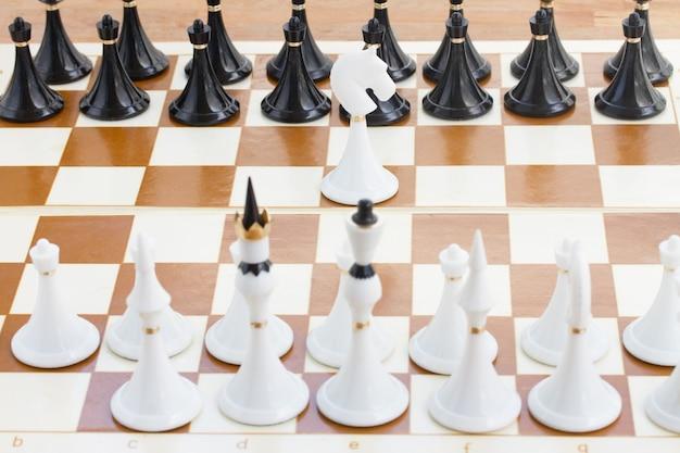 黒いチェスの列の前にいる単一の白い騎士