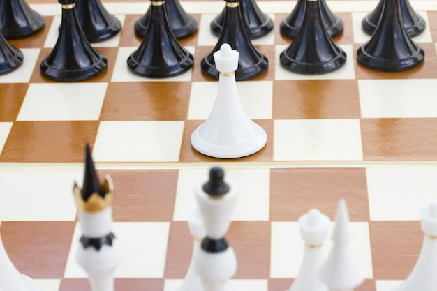 黒いチェスの前にある1つの白いポーン