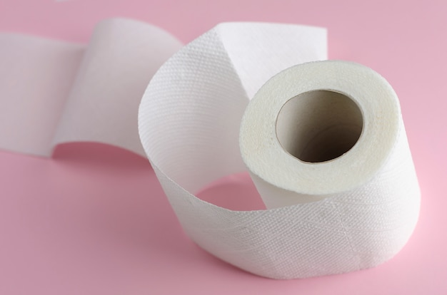 Single white toilet paper roll on pastel pink.