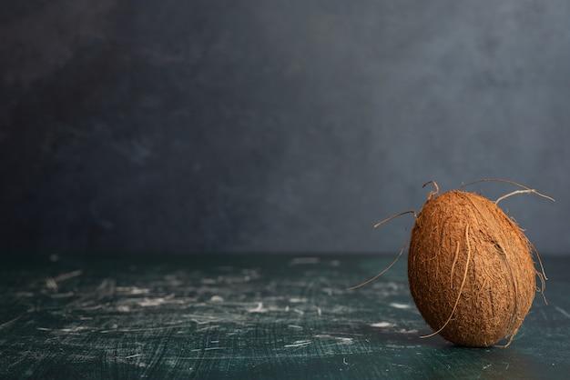 Singola noce di cocco intera sul tavolo di marmo