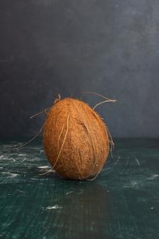 Singola noce di cocco intera sul tavolo di marmo.
