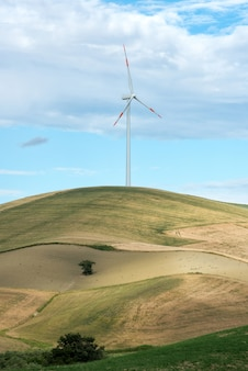 Single wind turbine in farmland on a hilltop