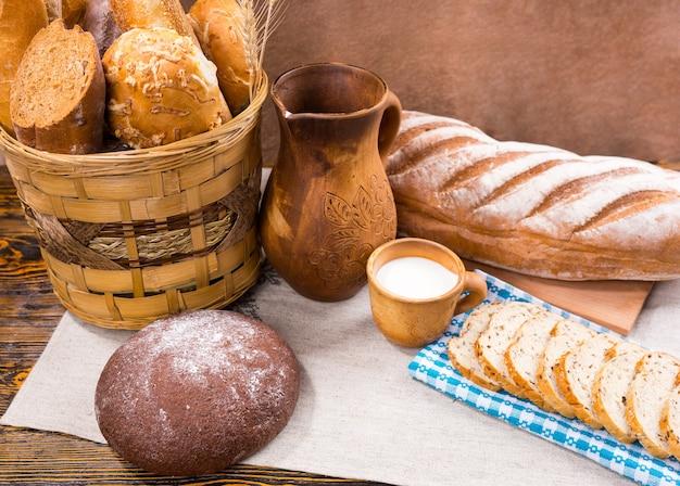Один деревянный кувшин, полная чашка молока и свежеиспеченный хлеб в виде цельного хлеба и ломтики рядом с корзиной на столе