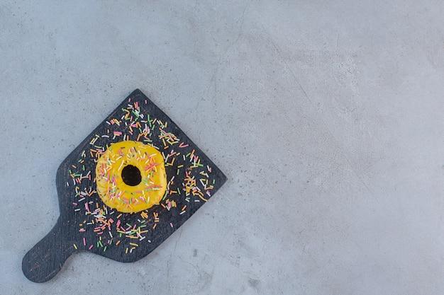 Ciambella gialla singola decorata con granelli sul tagliere.
