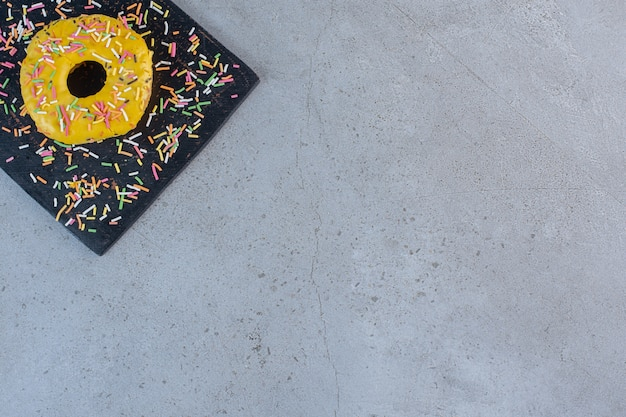 커팅 보드에 스프링클이 장식된 단일 노란색 도넛입니다.
