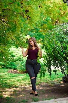 シングル若いかなりプラスサイズ白人幸せな笑みを浮かべて笑っている女の子女、夏の緑の森を歩きます。楽しい夏の屋外の自然をお楽しみください。