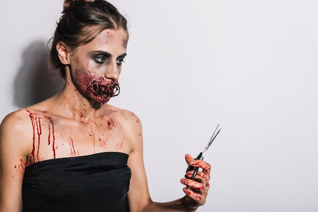 Sinister female with sewn mouth and scissors