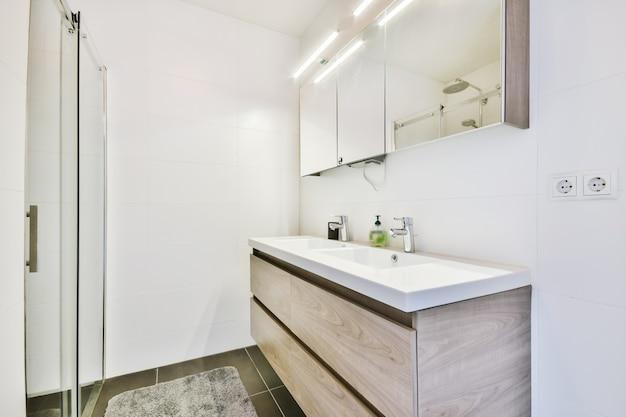 Напольный шкаф под раковину и зеркальный шкаф в облицованной белой плиткой ванной комнате с подвесным унитазом