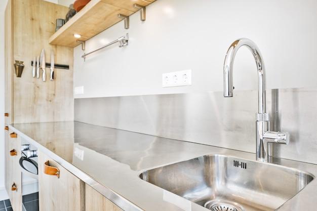 自宅のキッチンでスパイスとガスストーブを備えた瓶の近くのモダンなカウンターの下に設置された光沢のある蛇口でシンク