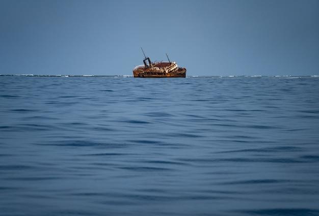 沈没した難破船がさびた古い海の真ん中に横たわっている