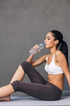 운동 후 물 한 모금. 회색 배경에 운동 매트에 앉아 있는 동안 운동복 식수를 입은 아름다운 젊은 아프리카 여성의 측면