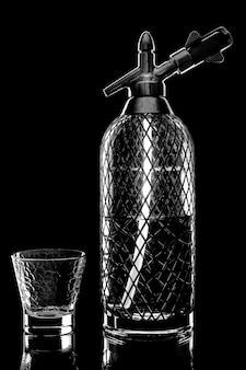 Сифон со спариванием соды на столе на черном фоне с пустой чашкой