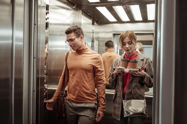 Потягивая капучино. жена потягивает капучино на вынос, поднимаясь в лифте со своим мужчиной