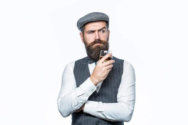 最高級のウイスキーを飲みます。厚いひげを持つ男の肖像画。古いウイスキーのグラスを持っているスタイリッシュな金持ち。