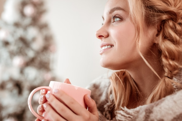 温かい飲み物を飲みます。大きな青い目で脇を見ている2つの三つ編みの完璧な長髪の女性