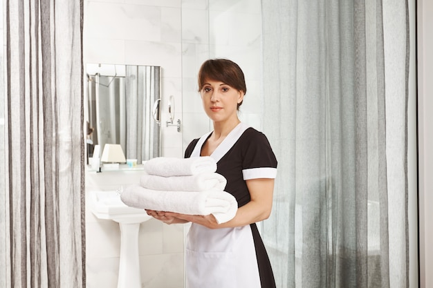 Sir, i will put extra towels in bathroom. portrait of woman in maid uniform standing with white hotel towels near door with calm and serious expression, being on work in hotel