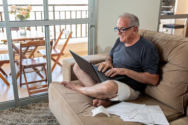 ノートパソコンでタイピングし、コロナウイルスによるパンデミックの時にホームオフィスシステムで自宅で仕事をしています。主は家で薄着を着て、マスクを横にして働いています。
