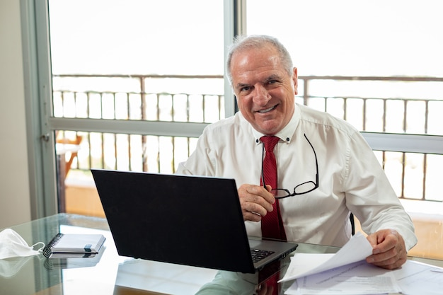 ノートブックでタイピングをして、ホームオフィスシステムで作業している。ミスターはシャツを着て自宅で働いていて、マスクを横にしてネクタイをしています。