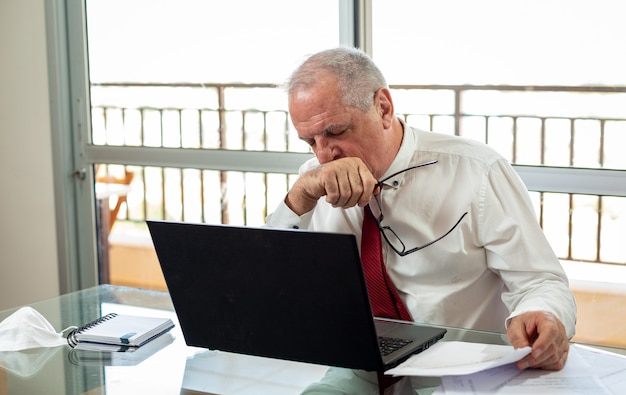 Sir typing and working on the home office system. he works wearing a shirt and tie with the mask left beside. expression of tiredness and discouragement.