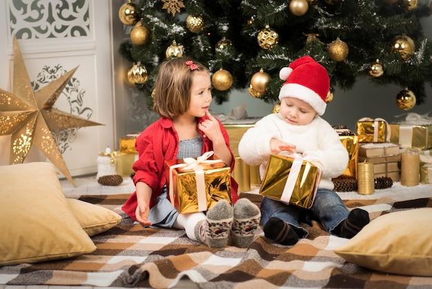姉と弟が飾られた木の近くでクリスマスプレゼントを贈る家族の休日