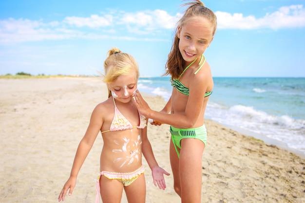 幼い子供に保護日焼け止めを塗っている姉妹。女の子は彼女の胃に日焼け止めクリームを描きます。
