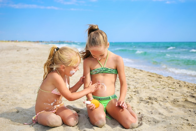 Sister applying protective sunscreen on young child.