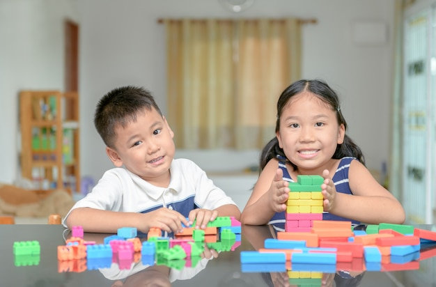 Sister and brother play wood brick tower,