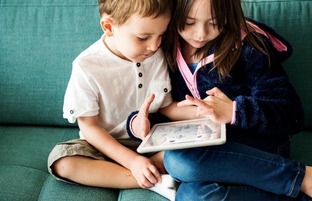 ティザーデジタルデバイスをプレイしている姉妹ブラザー