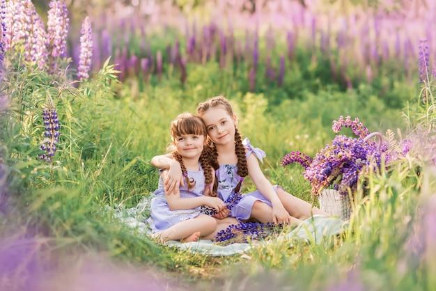 Сестра подруги на природе. девушки в сиреневых платьях сидят на траве.