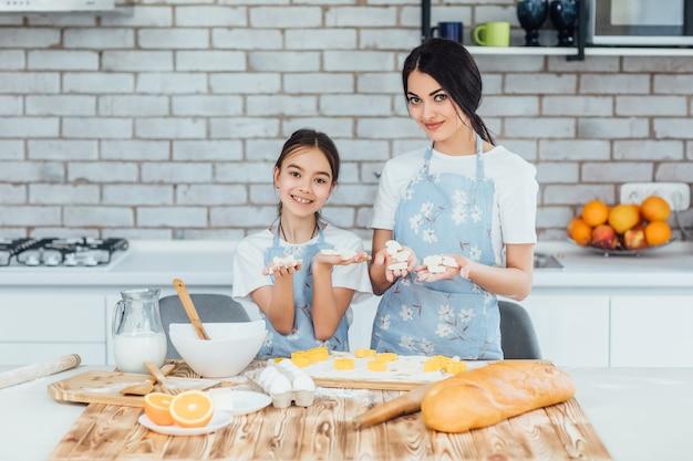 부엌에서 린저 쿠키를 요리하는 자매 소녀들