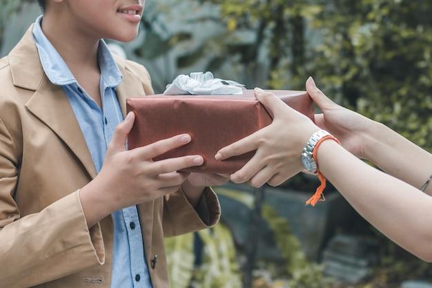 Сестра дает подарок, удивляющий молодого брата, чтобы вернуться домой в сад