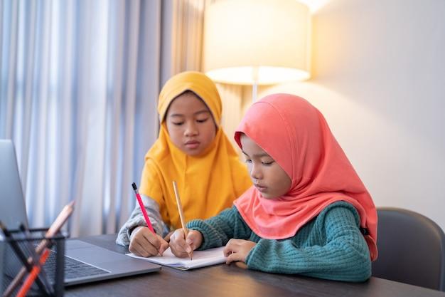 집에서 저녁에 숙제를 서로 돕는 자매
