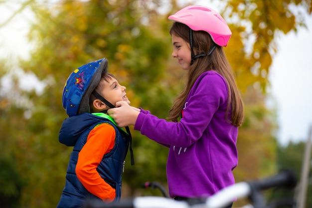Сестра помогает младшему брату надеть и застегнуть защитный шлем для велосипеда. концепция отдыха и проведения времени.