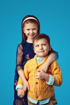 Сестра в синем платье обнимает своего брата, изолированного на синем фоне