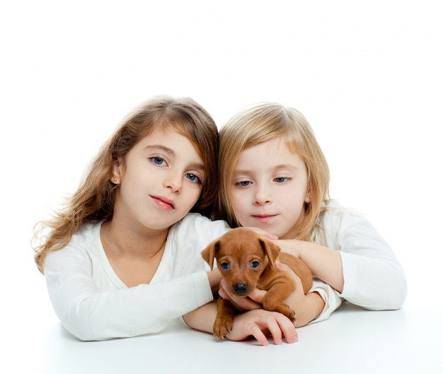 Sister kid girls and puppy mascot mini pinscher