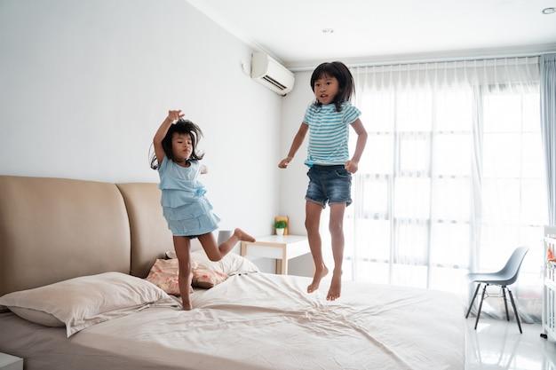 ベッドの上で楽しんでいる姉妹子供