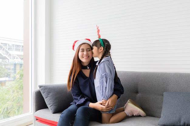 Сестра целует азиатскую сестру в щеку в гостиной.