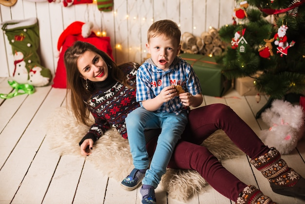 Sister and little brother in front of christmas tree