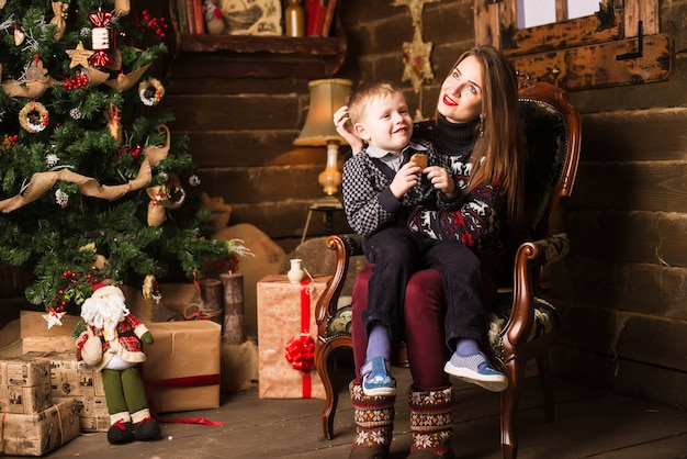 Sister and little brother sitting in front of christmas tree